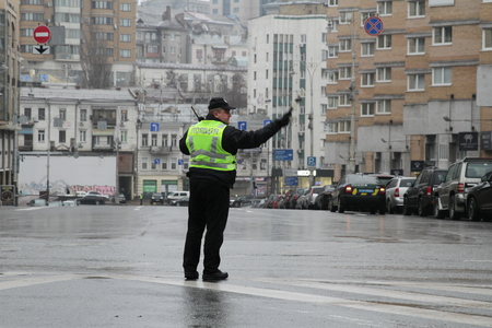 Kiev, Ukraine - November 29, 2017. Policeman regulates traffic at the crossroads in Kiev. Banco de Imagens - 90729979
