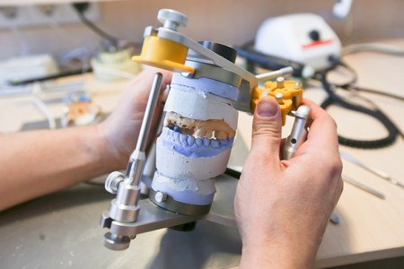 The master makes dental crowns for dentistry. Manufacture of dental crowns. Stock Photo