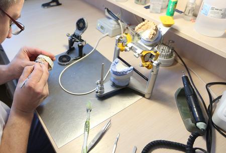 The master makes dental crowns for dentistry. Manufacture of dental crowns. Zdjęcie Seryjne