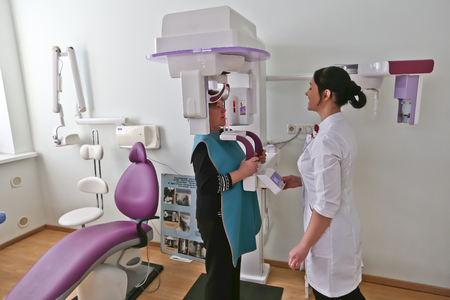 Close up head shot of girl taking dental tac with cephalometric panorama x-ray machine in clinic.