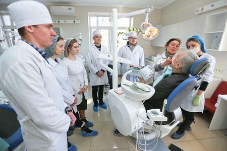Students practicing dentistry on medical dummies in a teaching facility or university