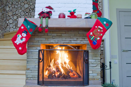 Fireplace with Christmas decorations. The firewood is burning in the fireplace