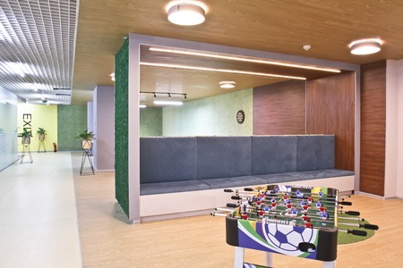Table soccer in a large office room. Interior of the staff rest room in the modern office of the business center. A table football game near a long sofa.