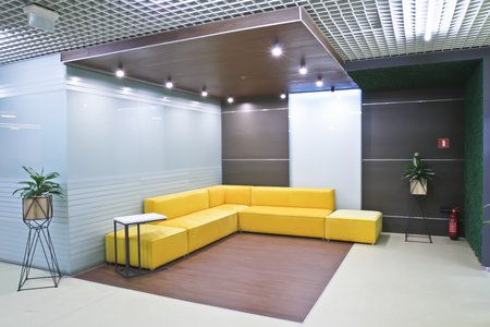 Interior reception in the modern office of the business center. Yellow corner sofa in the office reception. Exit the office.