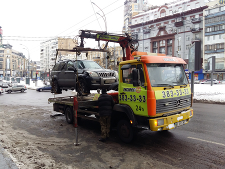 Kiev, March 6, 2018, Ukraine. Traffic police officers on street to pick up intruders car on tow truck. Loading tow truck car of violator of parking rules to tow truck