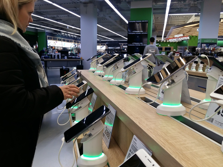Kiev, March 6, 2018, Ukraine. The buyer chooses a smartphone on the counter in one of the electronics supermarkets in Kiev.