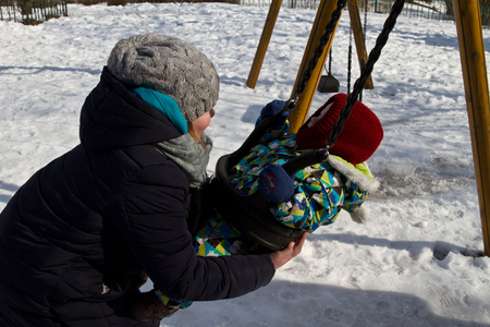 Kiev, 24 March 2018, Ukraine. Mother rolls her child on a swing. Child on swing in winter. Redactioneel