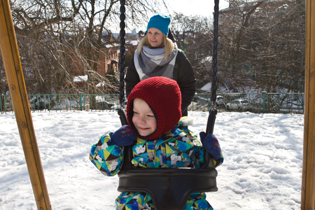 Kiev, 24 March 2018, Ukraine. Mother rolls her child on a swing. Child on swing in winter. Stockfoto