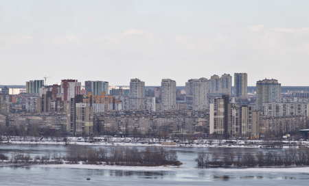 Kiev, March 24, 2018, Ukraine. View of the city and real estate through the winter river in the ice.