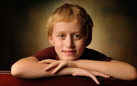 10 year old: Portrait of a cheerful 10 year old boy on a brown background