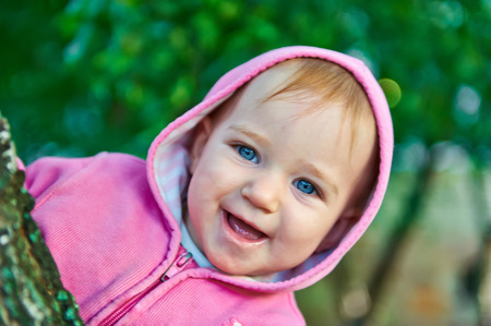 gaily: Little girl with blue eyes peered out from behind a tree smiling gaily