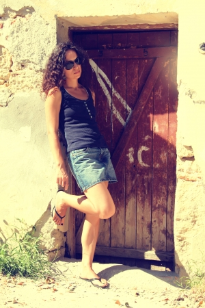 A girl stands leaning on an old wall. she was tired, her sunglasses. photo