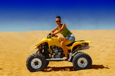 Girl sitting on the quad, in the middle of the desert. Stock Photo - 24087703
