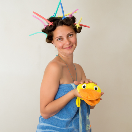 The photo shows a girl in a towel and curlers. Stock Photo