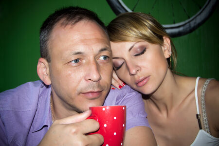 drowsiness: The photo shows a young man and a young woman. They sit at a table in his hands a cup. Stock Photo