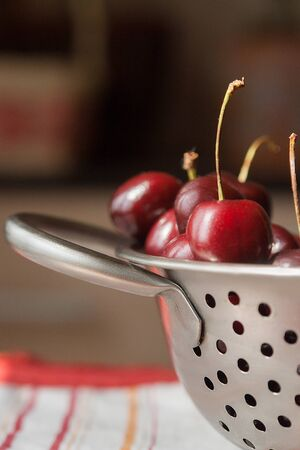 a colander: sweet cherries on metal colander Stock Photo