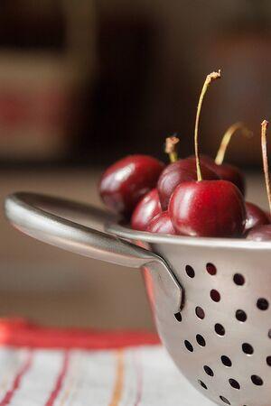 sweet cherries on metal colander Stock Photo