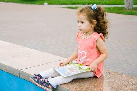 favorite book: Little baby girl reading her favorite book sitting on a park