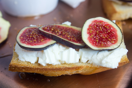 Bruschetta with goat cheese and figs on a coppet tray.