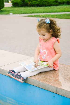 Little baby girl reading her favorite book sitting on a park.