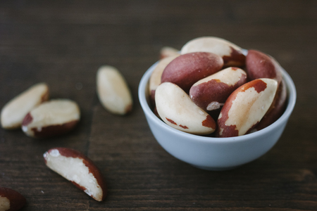 Brazil nuts on white ceramic bowl over the wooden table.