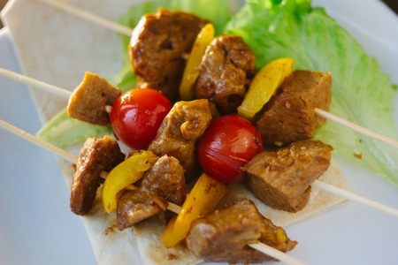 Seitan kebabs on white plate with the vegetables