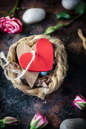 bounded: Two hearts bounded together on nest over black background. Stock Photo