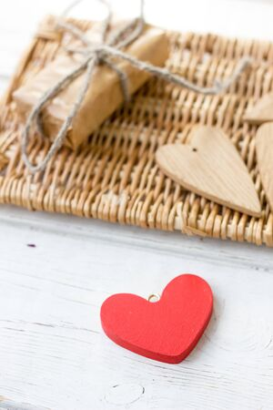 One red and few brown wooden hearts - gift for Valentines day.