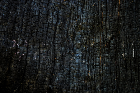 Black burnt wooden surface background. Dark ash and cinder surface.