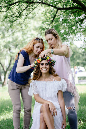 Putting a flower wreath to the hairs of young beautiful model.