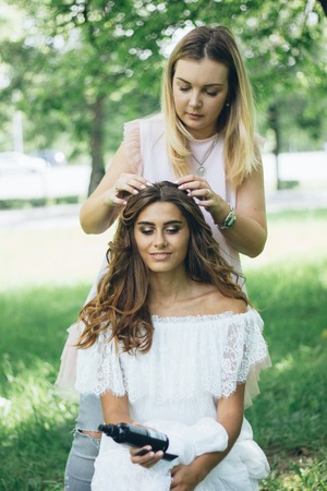 Hairdressing, Master create beautiful hairstyle for young woman.