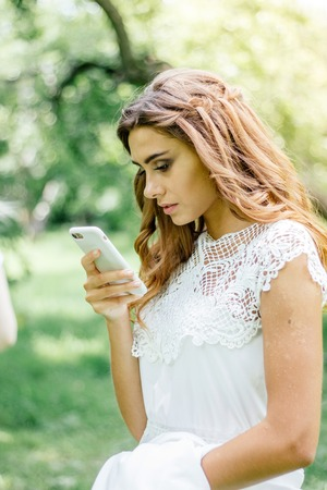 Beautiful young bride chating by mobile phone during wedding