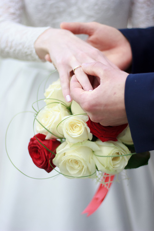 arm bouquet: Groom put the wedding ring to bridal hand.