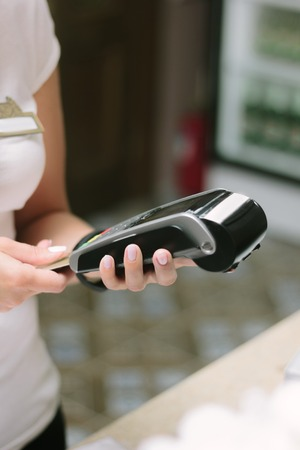 card making: Operator making a sale with pos terminal and credit card. Stock Photo
