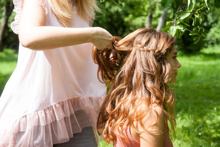 Hairstylist braiding pigtails to young girl outdoor. Creating braids. Stock Photo