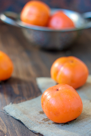 Group of persimmons on wooden table and piece of fabric.