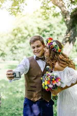 Young couple - bride and groom making selfie during wedding ceremony.