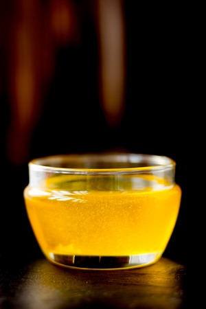 Nice ghee in a glass bowl over black background.
