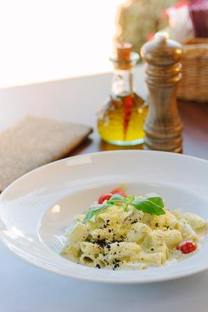 Italian food - rigatoni pasta with basil and black truffle.