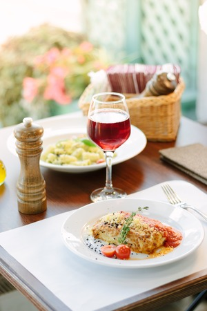 Italian food - delicious lasagne in white plate on table with red wine.