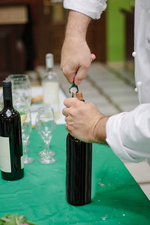 Sommelier opens the bottle with red wine.