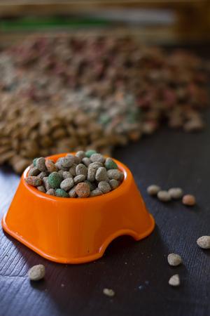 plastico pet: Plastic bowl with dry pet food on black wooden board Foto de archivo