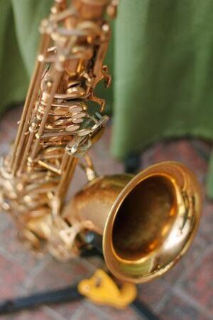 Golden saxophone staying on the rack Stock Photo