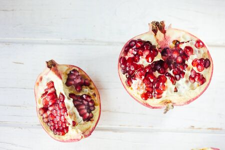 Parts of fresh pomegranate over white wooden surface.