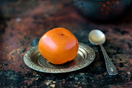Ripe persimmon on metal plate over black rustic surface.