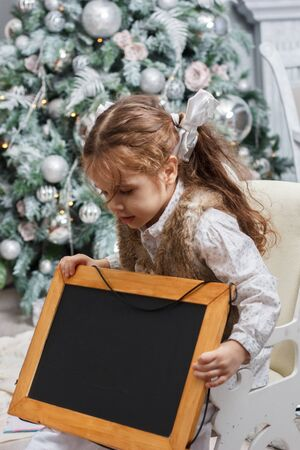Little kid looks to black board in shees hands. Christmas tree as background. Stock Photo