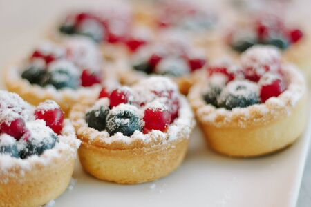 Tartlets with blueberries and raspberry. Small tarts with fruits.