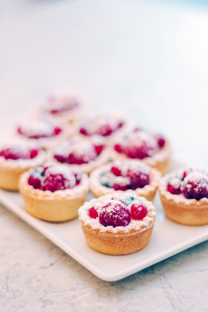 Small tarts with berries on white plate. Foto de archivo