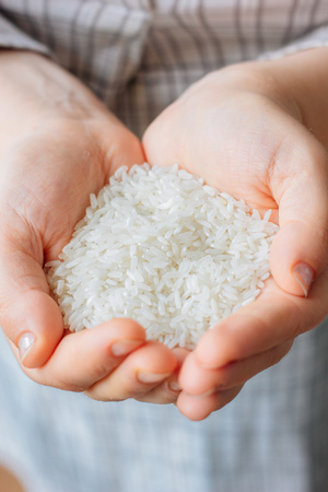 Woman hands holding a white rice.