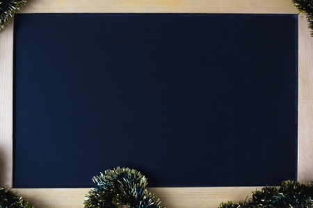 Blackboard with place for your text, surrounded by christmas garland.